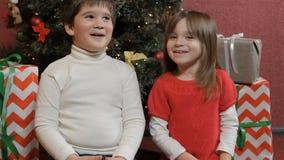 Kids share secrets near the christmas tree stock video