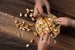 3 kids sharing eating popcorn in a bowl. On a wooden table background. sharing concept Stock Images