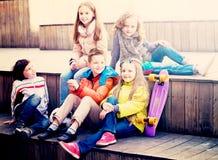 Kids sharing secrets as talking. Happy little boys and girls sharing secrets as talking outdoor stock photo
