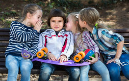 Kids sharing secrets as talking outdoor Stock Photos