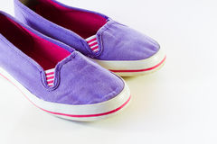 Kids' shoes. Colorful purple and pink canvas kids' shoes on pale background Stock Photography