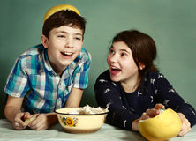 Kids  siblings  peeling grape fruit make funny hat Royalty Free Stock Images