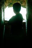 Kids Silhouette. Young kid inside a cave like looking to the sea Stock Image