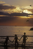 Kids at Silhouette. Three kids playing in the ocean Royalty Free Stock Photo