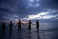 Kids at Silhouette. Five kids playing in the ocean Stock Photography