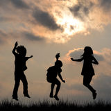 Kids silhouette jumping outdoor Stock Images