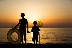 Kids silhouettes on beach Stock Image