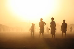 Kids silhouettes in the dusty sunset. (Shibam, Yemen stock photography