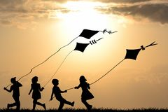 Kids silhouettes playing with kites. At sunset royalty free stock images