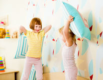 Kids sisters play with pillows in the bedroom Stock Image