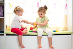Kids sisters play together indoors Royalty Free Stock Images