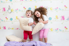 Kids sisters playing by pillows Royalty Free Stock Images