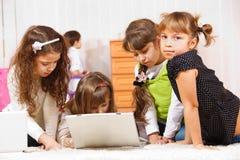 Kids sit around laptop Royalty Free Stock Images