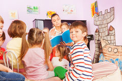 Kids sit around teacher and listening to story. Group of kids sit around teacher and listening to the story she reading with one boy turn back to camera Royalty Free Stock Images