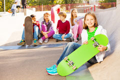 Kids sit behind and girl in front with skateboard Stock Images