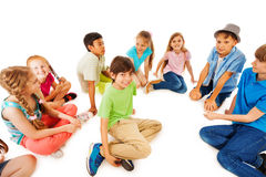 Kids sit in circle with one boy at center. Group of kids sit in the circle with one boy in the center happy and smiling, isolated on white Stock Photography