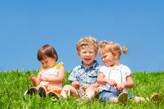 Kids sit on grass Royalty Free Stock Photography