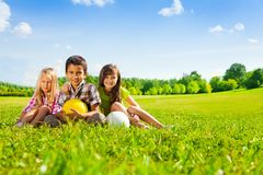 Kids sit in the grass with sport balls. Three happy kids, boy and girls sitting in the sunny summer park holding sport balls royalty free stock photography