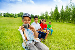 Kids sit in row and boy with camera smiling Stock Photography