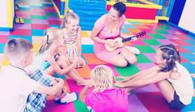 Kids sitting around teacher with small guitar Stock Images