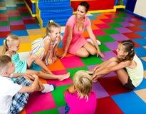 Kids sitting around teacher and talking. Smiling kids sitting around teacher and talking in class stock image