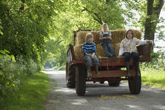 Kids Sitting On Back Of Trailer On Country Lane Royalty Free Stock Photography