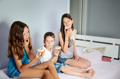 Kids are sitting in bed and eating donuts Royalty Free Stock Photo