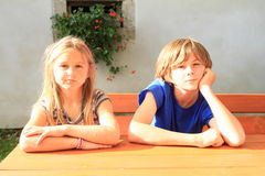 Kids sitting behind wooden table Royalty Free Stock Photo