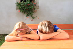 Kids sitting behind wooden table Stock Photos