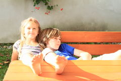 Kids sitting behind wooden table. Two kids - boy leaning on a smiling girl sitting behind a wooden table with bare feet on the table Royalty Free Stock Photography