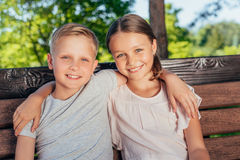 Kids sitting on bench in park. Portrait of smiling kids hugging each other while sitting on bench in park royalty free stock images