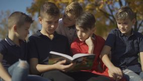 Kids sitting on the bench and riding one book. Friends spend time riding book on a sunny day in the autumn park. stock video