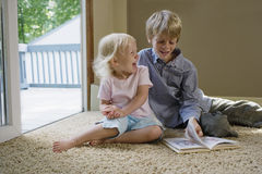 Kids Sitting On Carpet With Book. Young boy with sister sitting on carpet with book laughing Stock Photography