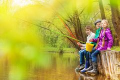 Kids sitting and fishing together near the pond. With colorful fishrods in beautiful forest landscape Royalty Free Stock Photos