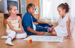 Kids sitting on floor with game Stock Photos