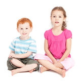 Kids sitting on floor isolated. Two kids sitting on floor cross legged. Isolated on white stock photos