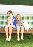Kids sitting on a garden swing with dogs Stock Photography