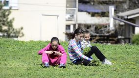 Kids Sitting in Grass Field Royalty Free Stock Photos