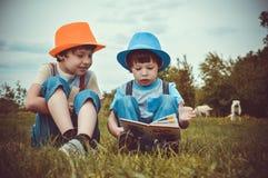 Kids Sitting On Green Grass Field stock photo