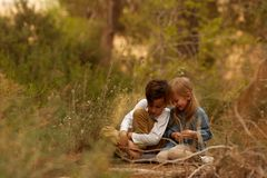 Kids sitting on ground in nature royalty free stock images