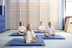 Kids sitting on mats. Kids sitting cross-legged on blue mats in the school gym Royalty Free Stock Images