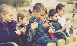 Kids sitting with mobile devices outdoor. Positive kids sitting on bench with mobile devices outdoor stock images