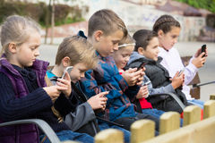 Kids sitting with mobile devices. Positive kids sitting on bench with mobile devices in street stock image
