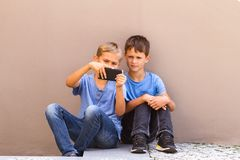 Kids sitting outside and playing games on smartphone stock photography