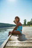 Kids sitting on a pier in summer Royalty Free Stock Photo