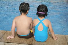 Kids sitting by the pool. Little kids sitting and playing by the pool Stock Photography
