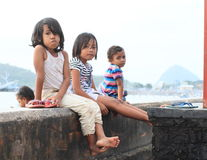 Kids sitting on railings in Labuan Bajo. Poor barefoot kids sitting on concrete railings in Labuan Bajo (Flores, Indonesia Royalty Free Stock Photos