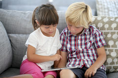 Kids sitting on sofa and playing games Royalty Free Stock Photography