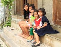 Kids sitting on stairs in Yogyakarta. Barefooted kids - indonesian girls and boys sitting on stairs in Yogyakarta (Java, Indonesia Stock Photos
