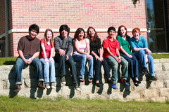 Kids sitting on stone wall. Diverse group of multi-ethnic teens sitting on stone wall Royalty Free Stock Photos